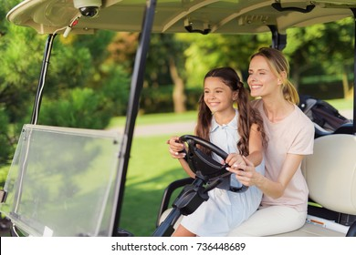 A girl with a woman will play golf. The girl is sitting on her knees and they drive the car together.