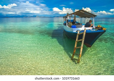 Girl in a wooden boat on a snorkeling trip anchored in clear ocean waters on the shore of Flores Island, Indonesia