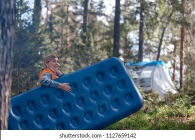 A girl in the woods carries an air mattress