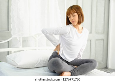 The girl wore a white clothes after waking up in bedroom, Twisting the body from drowsiness and fatigue