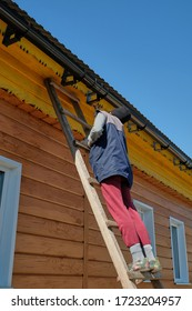 a girl in work clothes and a hat stands on a ladder and paints the roof of the house in yellow.
