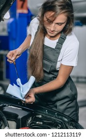 A girl worker in a black jumpsuit and a white t-shirt checking the oil level in a black car in the garage.