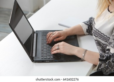 The girl working behind the laptop at the Office. On a white background