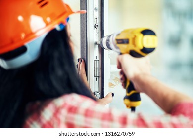 The girl in working clothes does the repair