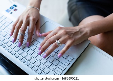 A girl working with her laptop in office or co working space . Fingers with silver rings and pink manicure .