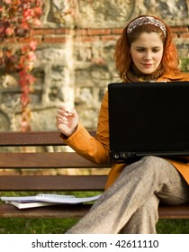 A girl working with a laptop sitting on a bench with colorful fall background