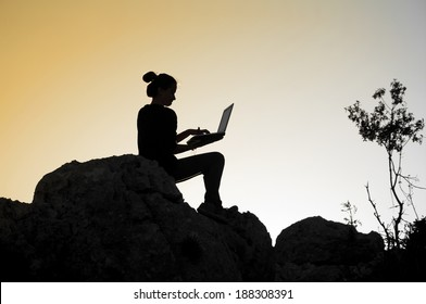 Girl working with laptop at sunset