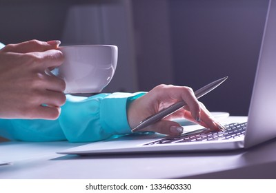 The girl is working late in the dark office with laptop. Young businesswoman girl in office. Close-up photo of a businesswoman working on a laptop in a dark room.