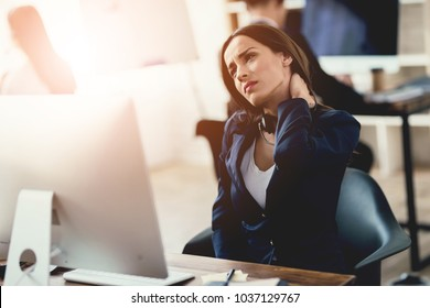 A girl working in the office feels tired. She has a sore neck, which she massages. She works in the call center. Tired woman at work.