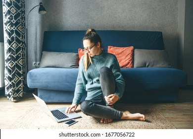 Girl working on laptop from home or student studying from home or freelancer. Or she is watching a video or using the Internet