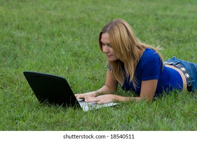 Girl working on laptop laying on grass