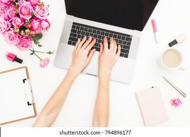 Girl working on laptop. Office workspace with female hands, laptop, pink roses bouquet, coffee mug, diary on white table. Top view. Flat lay.