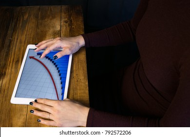 The girl working with a tablet computer. The graph rises. Table, wooden, background black.