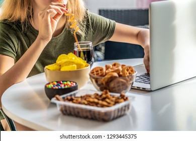 Girl works at a computer and eats fast food. Unhealthy food: chips, crackers, candy, waffles, cola. Junk food, concept.