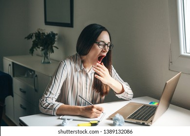 A girl works at a computer in a home office or a student at home teaches lessons. She is tired, yawns and wants to sleep or is bored.
