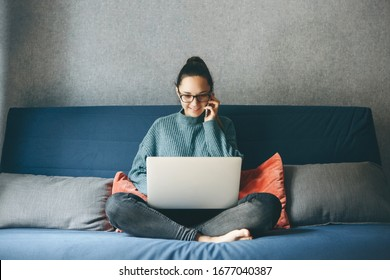 A girl works from home or a student is studying from home or a freelancer. She uses a laptop and a phone.