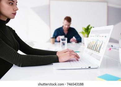 Girl works on a laptop with company statistics. Concept of internet sharing and interconnection