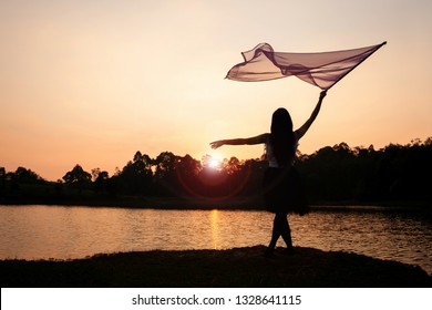 Girl Worship Jesus with Flag Dance in the Sunset at the River. Flare Added.