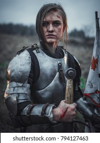 Girl with wounds on her face in image of Joan of Arc (Jeanne d'Arc) in armor stands with flag in her hands and sword on meadow against background of grass and sky. Portrait.
