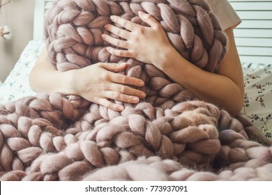 Girl wrapped in big merino wool blanket sitting on the bed
