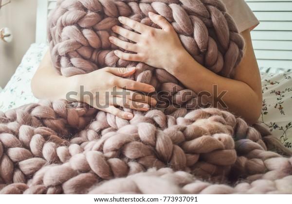 大きなメリノの毛布で包まれた女の子がベッドに座っている