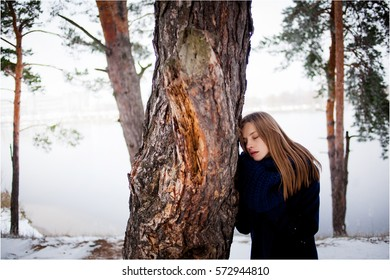 girl wrapped in a blue coat and a blue knitted scarf walking in winter snow-covered pine forest. Walk through the winter snow-covered pine forest near the lake. Women's emotional portrait.