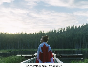 Girl wrapped in Canada flag during sunset at a lake