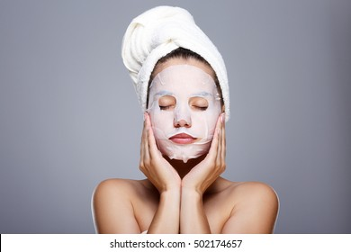 Girl with wrapped hair with towel. Closed eyes, touching skin covered by mask. Model with white face, has mask on face. Head and shoulders, studio, indoors