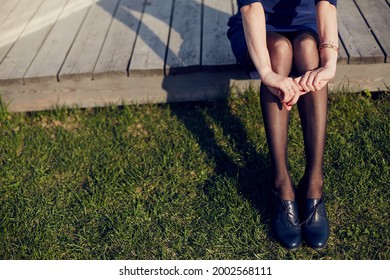The girl wrapped her arms around her legs. Grass.