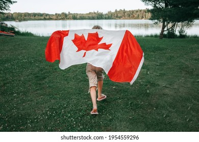 Girl wrapped in large Canadian flag by Muskoka lake in nature. Canada Day celebration outdoors. Kid in large Canadian flag celebrating national Canada Day on 1 of July.