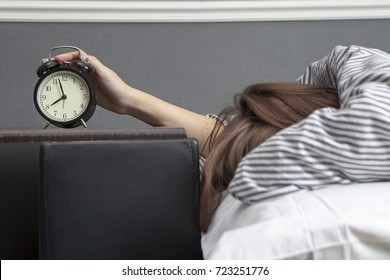 The girl, wrapped in a striped blanket, puts out her hand to turn off the alarm. There is eight hours on the alarm clock.