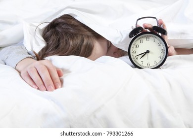 The girl, wrapped in a white blanket, puts out her hand to turn off the alarm. There is eight hours on the alarm clock.