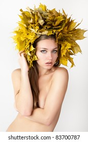 A girl with a wreath of autumn leaves on the head.