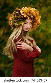 Girl in a wreath of autumn maple leaves. Queen and Autumn leaf fall. Beautiful, thoughtful, dreamy, enigmatic smile. The girl in the red dress. Woman with wreath of leaves on a head, outdoor portrait