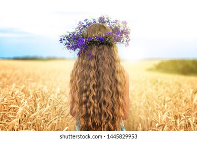 Girl with a wreath of flowers on her head in a wheat field, enjoys nature. Free happy woman