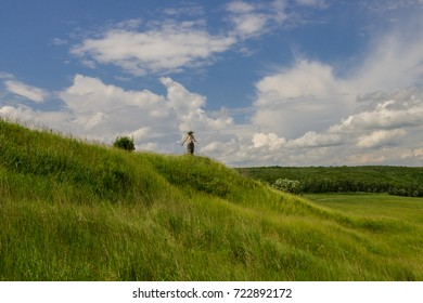 girl in a wreath on a hill, is arms outstretched