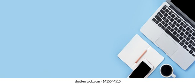 Girl write on open white book or accounting on a minimal clean light blue desk with laptop and accessories, copy space, flat lay, top view, mock up
