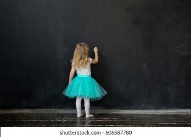 Girl writes with chalk on a blackboard