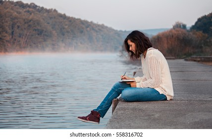 Girl writes diary by lake