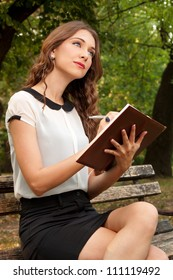 The girl writes her diary in the park