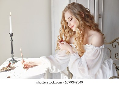 Girl writes a letter to her beloved man sitting at home at the table in a white light dress, purity and innocence. Curly blonde romantic look, beautiful eyes. White wildflowers on the table