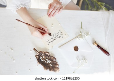 Girl writes a letter to her beloved man, sitting at home at table in a white light dress, purity and innocence. Curly blonde romantic look, beautiful eyes. White wildflowers on the table. Perfect body