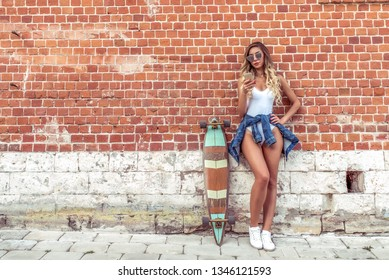 Girl writes message phone, skateboards, longboard. Fashionable and stylish white body bathing suit. Online application Internet, social networks. Free space. Summer city brick wall background.