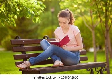 girl writes in a notebook, sitting on a bench in the Park