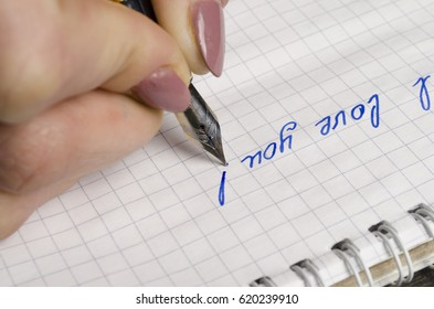 Girl writes on a piece of paper with a pen