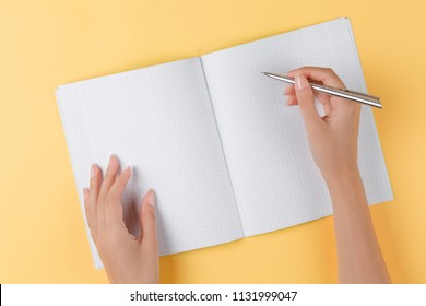 girl writes in an open notebook top view on yellow background, office desk in the flat lay. women write in a notebook