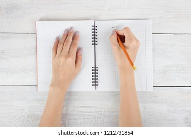 Girl writes in pencil in notebook on wooden background. Top view.