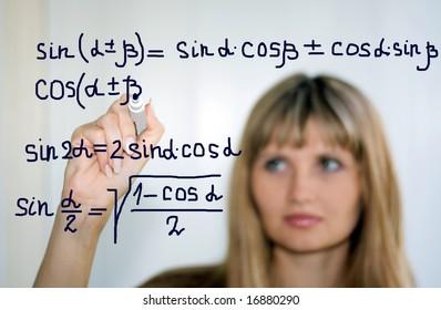 girl writing math formulas on a white-board