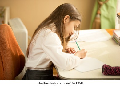 Girl writing in notebook with pencil at her bedroom