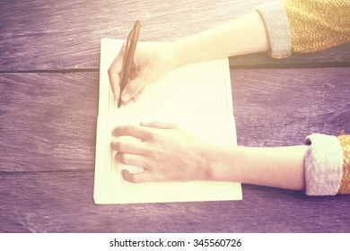 Girl writing with pen in blank diary on wooden table, instagram photo effect